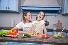 一个美丽的年轻母亲和女儿获得乐趣,当准备他们的在蓝色厨房前面时的膳食 库存图片