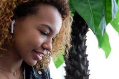 一个美丽的年轻现代黑人妇女的画象,有airpods的皮夹克的在她的耳朵,听到音乐 破擦声 免版税图库摄影