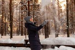 一个美丽的年轻白肤金发的女孩在冬天具球果森林是站立和捉住用她的手落从的雪 免版税图库摄影