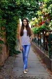 一个美丽的微笑的女孩在街道上站立反对backgr 库存图片