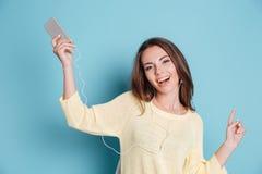 一个美丽的微笑的女孩的特写镜头画象有耳机的 库存图片