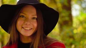 一个美丽的微笑的女孩的画象黑帽会议的有在前景的一黄色枫叶的在秋天森林里 影视素材