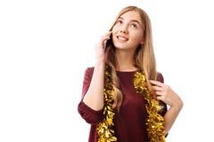 一个美丽的微笑的女孩的画象,穿戴在一件红色礼服,谈话在一个手机,站立和看对边,孤立 库存照片