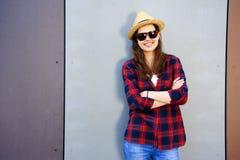 一个美丽的微笑的女孩的画象红色衬衣和帽子的,玻璃 库存图片