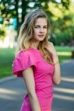 一个美丽的微笑的年轻逗人喜爱的女孩的画象一件桃红色夏天礼服的 库存图片