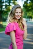 一个美丽的微笑的年轻逗人喜爱的女孩的画象一件桃红色夏天礼服的 免版税图库摄影