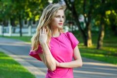 一个美丽的微笑的年轻逗人喜爱的女孩的画象一件桃红色夏天礼服的 免版税库存图片