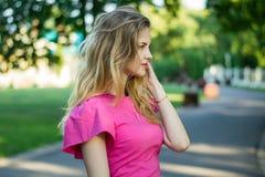一个美丽的微笑的年轻逗人喜爱的女孩的画象一件桃红色夏天礼服的 免版税库存照片