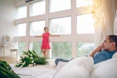 一个美丽的怀孕的女孩在一个大全景窗口附近站立 她在短的桃红色礼服打扮并且看给她 免版税库存图片