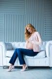 一个美丽的怀孕的女孩坐在企业样式的一个沙发 库存照片