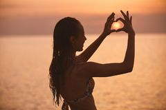 一个美丽的性女孩的剪影反对海和日落的 图库摄影