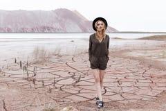 一个美丽的性感的女孩的时尚射击黑帽会议的在杂志的沙漠被去除 图库摄影