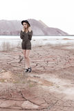 一个美丽的性感的女孩的时尚射击黑帽会议的在杂志的沙漠被去除 库存图片