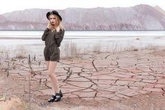 一个美丽的性感的女孩的时尚射击黑帽会议的在杂志的沙漠被去除 免版税库存图片