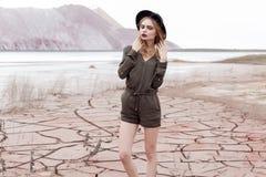 一个美丽的性感的女孩的时尚射击黑帽会议的在杂志的沙漠被去除 免版税库存照片