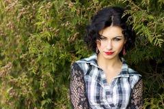 一个美丽的性感的女孩的画象有红色嘴唇的深色与卷毛在公园走 免版税库存图片