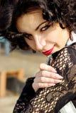 一个美丽的性感的女孩的画象有红色嘴唇的深色与卷毛在公园走 免版税库存照片