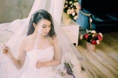 一个美丽的性感的嫩新娘的画象有长的黑或黑发的在早晨在家坐床 古典 免版税库存照片