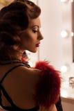 一个美丽的性感的少妇的画象有减速火箭的发型鞋带女用贴身内衣裤的有毛皮的坐肩膀在镜子附近  免版税库存照片