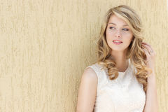一个美丽的性感的微笑的愉快的女孩的画象有大充分的嘴唇的有在一件白色礼服的金发的在一晴朗的明亮的天 免版税库存照片