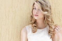 一个美丽的性感的微笑的愉快的女孩的画象有大充分的嘴唇的有在一件白色礼服的金发的在一晴朗的明亮的天 免版税图库摄影