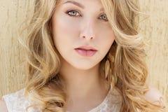 一个美丽的性感的微笑的愉快的女孩的画象有大充分的嘴唇的有在一件白色礼服的金发的在一晴朗的明亮的天 免版税库存图片