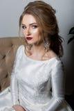 一个美丽的性感的逗人喜爱的女孩愉快的新娘的画象一身庄重装束的与在一件白色礼服的明亮的构成有一个华美的婚礼的 免版税库存照片