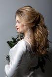 一个美丽的性感的逗人喜爱的女孩愉快的新娘的画象一身庄重装束的与在一件白色礼服的明亮的构成有一个华美的婚礼的 库存图片