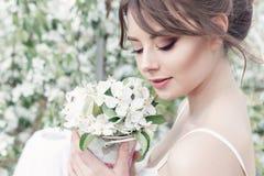 一个美丽的性感的逗人喜爱的女孩新娘的画象一件白色礼服的有晚上的精美构成和发型的与一束的d 图库摄影