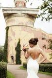 一个美丽的愉快的深色的新娘的画象握在花花束的婚姻的白色礼服的手户外 免版税库存照片