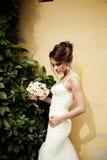 一个美丽的愉快的深色的新娘的画象握在花花束的婚姻的白色礼服的手户外 库存照片