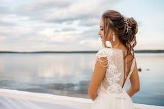 一个美丽的新娘在码头站立 浇灌在背景的表面和多云天空 库存照片