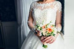 一个美丽的新娘在窗口附近站立并且拿着与白玫瑰和桃子牡丹的婚礼花束 特写镜头 库存照片