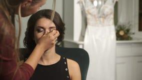 一个美丽的新娘的准备在婚礼之日 化妆师在鞭子女孩黏附假钻石 大日 股票视频