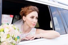 一个美丽的新娘的特写镜头画象在她的婚礼花束旁边在婚礼汽车的窗口里变老了 库存图片