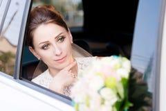 一个美丽的新娘的特写镜头画象在她的婚礼花束旁边在婚礼汽车的窗口里变老了 免版税库存图片