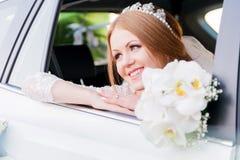 一个美丽的新娘的特写镜头画象在婚礼车窗里 婚礼幸福的概念 库存图片