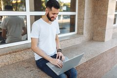 一个美丽的时髦的人的画象在一件白色T恤杉,穿戴了坐栏杆,与一台膝上型计算机一起使用,在街道上反对 免版税库存照片