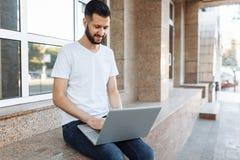 一个美丽的时髦的人的画象在一件白色T恤杉,穿戴了坐栏杆,与一台膝上型计算机一起使用,在街道上反对 免版税库存图片