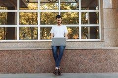 一个美丽的时髦的人的画象在一件白色T恤杉,穿戴了坐栏杆,与一台膝上型计算机一起使用,在街道上反对 库存照片