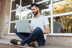 一个美丽的时髦的人的画象在一件白色T恤杉,穿戴了坐栏杆,与一台膝上型计算机一起使用,在街道上反对 免版税图库摄影