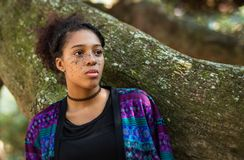 一个美丽的有雀斑的面孔褐色皮肤少妇的画象除一个生苔树干以外的 免版税库存图片