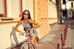 一个美丽的浅黑肤色的男人的室外时尚画象有自行车的 免版税库存照片