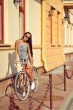 一个美丽的浅黑肤色的男人的室外时尚画象有自行车的 库存照片