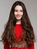 一个美丽的深色的女孩的画象有长的头发的在一位红色博士 免版税图库摄影