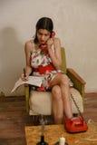 一个美丽的深色头发的女孩写下某事,当谈话由电话时 免版税库存照片