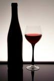一个美丽的瓶的剪影与一块玻璃的酒与在黑桌上的反射 库存图片