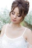 一个美丽的甜柔和的愉快的女孩的画象一件米黄礼服的有一种美好的闺房构成发型的,处理在t的照片 图库摄影