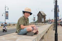 一个美丽的男孩的画象一个短的衬衣和帽子的 图库摄影