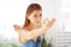 一个美丽的白肤金发的女孩伸她的在她前面的手,集中她的手指,保持平衡 免版税库存照片